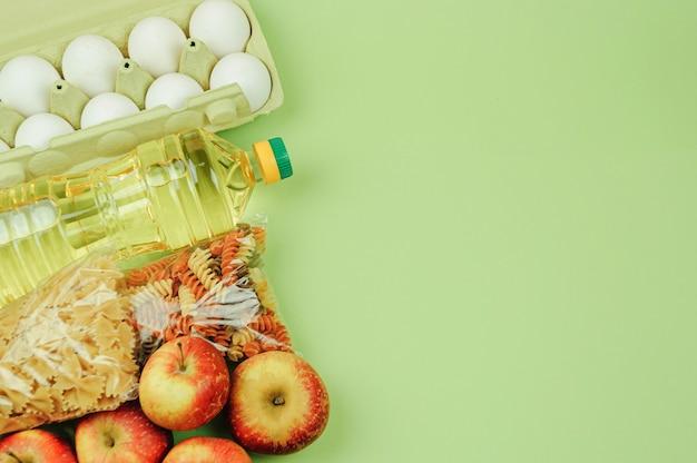 Widok z góry, makieta. ryż, konserwy, masło, jajka, jabłka, makaron. zakupy online.