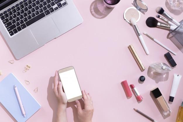 Widok z góry makieta telefonu komórkowego z białym pustym ekranem przestrzeni kopii w kobiecej dłoni. płaskie miejsce do pracy dla kobiet z laptopem, zestawem kosmetyków, papeterią i kwiatami, twardym światłem