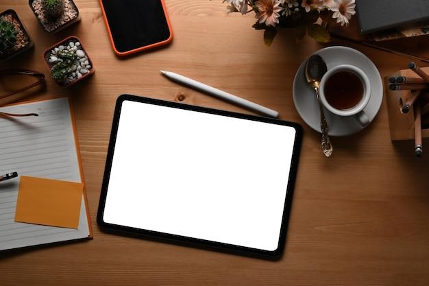 Widok z góry makiety cyfrowego tabletu, smartfona, notebooka i filiżanki kawy w obszarze roboczym freelancera.