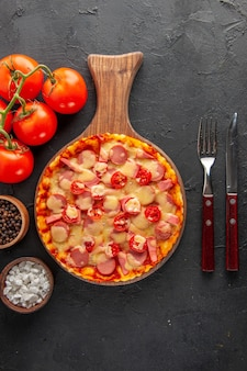 Widok z góry mała pyszna pizza z pomidorami i sztućcami na ciemnym stole