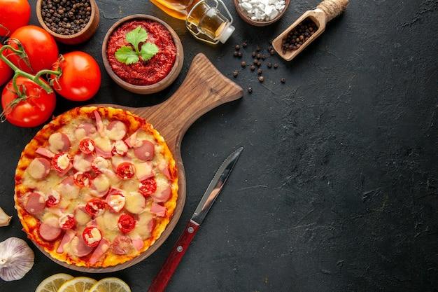Widok z góry mała pyszna pizza ze świeżymi czerwonymi pomidorami na ciemnym stole dostawa wolna przestrzeń