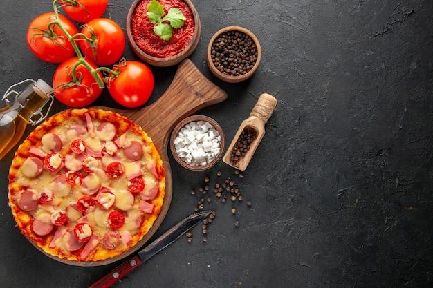 Widok z góry mała pyszna pizza ze świeżymi czerwonymi pomidorami na ciemnym stole