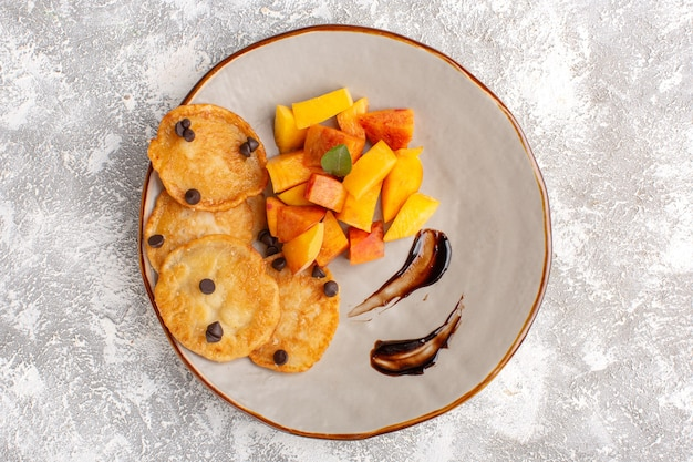 Widok z góry małe ciasteczka na talerzu ze świeżymi pokrojonymi brzoskwiniami na jasnym stole, ciasto biszkoptowe cukier słodkie ciasto zapiekane