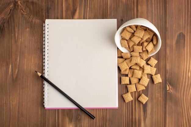 Widok z góry małe ciasteczka poduszkowe na brązowym drewnianym biurku