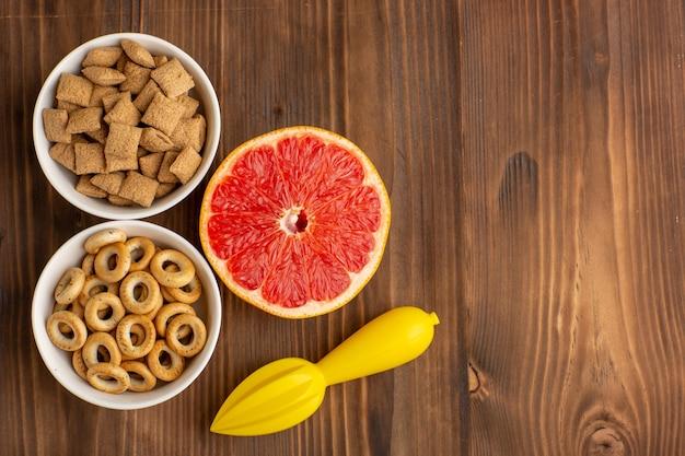 Widok z góry małe ciasteczka poduszkowe z krakersami i grejpfrutem na brązowym biurku