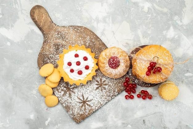 Widok z góry małe ciastka ze śmietaną i ciasteczkami na lekkim biurku z cukrem słodkim