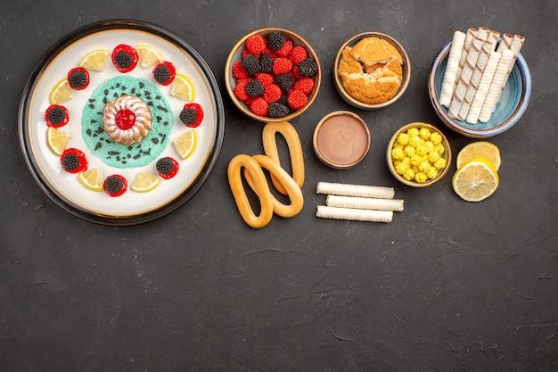 Widok z góry małe ciastko z plasterkami cytryny i cukierkami na ciemnym tle ciasto słodkie herbatniki owocowe ciastko cytrusowe