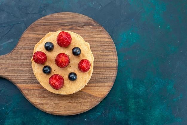 Widok z góry małe ciasto pieczone okrągłe uformowane ze świeżych truskawek na ciemnoniebieskiej powierzchni