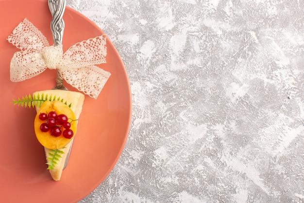 Widok z góry małe ciasto wewnątrz płyty w kolorze brzoskwiniowym na białym tle ciasto bsicuit słodkie ciasto cukrowe
