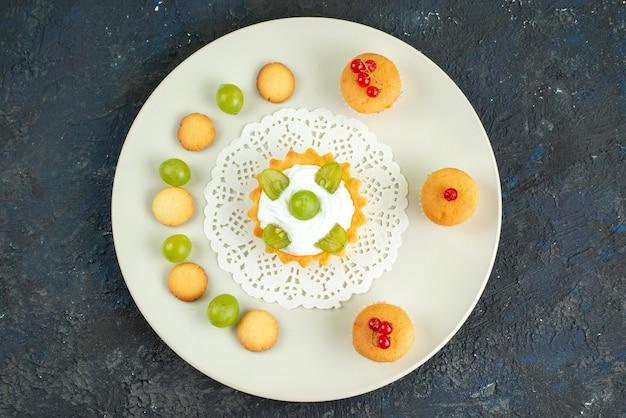 Widok z góry małe ciasto z kremem i zielonymi winogronami wewnątrz talerza wraz z ciasteczkami na jasnej powierzchni słodkie owoce