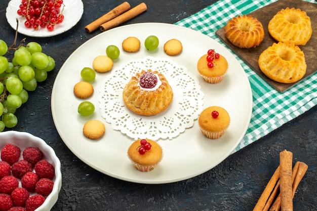Widok z góry małe ciasto z kremowymi ciasteczkami i zielonymi winogronami, malinami i żurawiną na ciemnym biurku słodkie