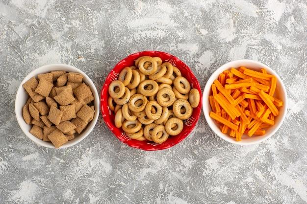 Widok z góry małe krakersy z ciasteczkami poduszkowymi i sucharkami na białym biurku