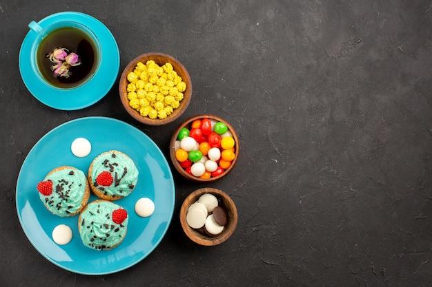 Widok z góry małe kremowe ciasta z filiżanką herbaty i cukierków na ciemnej powierzchni kolor deseru z kremem herbacianym