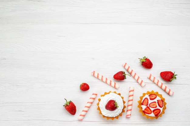 Widok z góry małe kremowe ciasta ze świeżymi truskawkami i cukierkami na jasnym tle ciasto słodkie zdjęcie owocowe wypieki jagodowe