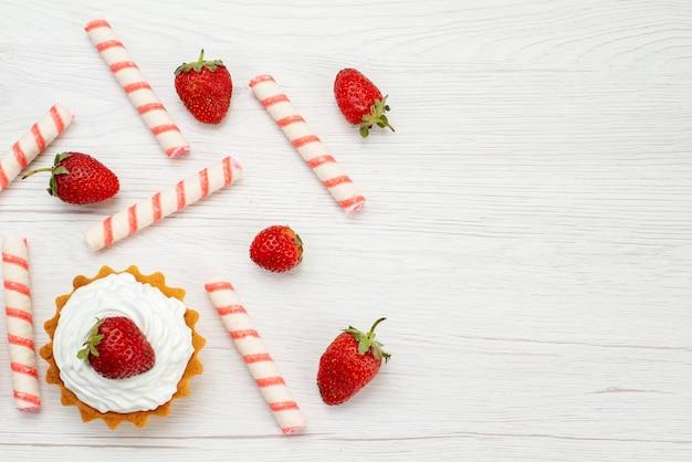 Widok z góry małe kremowe ciasta ze świeżymi truskawkami i cukierkami na lekkim biurku ciasto słodkie zdjęcie owocowe wypieki jagodowe