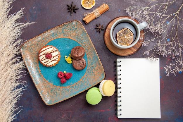 Widok z góry małe kremowe ciasto z czekoladowymi ciasteczkami i filiżanką herbaty na ciemnej powierzchni ciastko biszkoptowe słodkie ciasteczko z cukrem