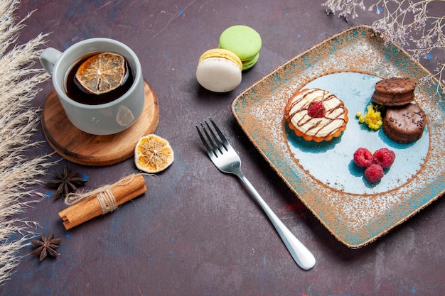 Widok z góry małe kremowe ciasto z czekoladowymi ciasteczkami i filiżanką herbaty na ciemnej powierzchni