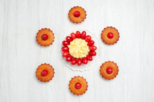 Widok z góry małe kremowe ciasto z dereniami i ciastami na białym biurku