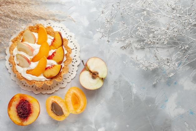 Widok z góry małe kremowe ciasto z pokrojonymi owocami i białą śmietaną oraz świeże morele i brzoskwinie na białym biurku ciasto owocowe herbatniki