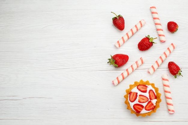 Widok z góry małe kremowe ciasto ze świeżymi truskawkami i cukierkami na jasnym tle ciasto słodkie zdjęcie owoce jagodowe piec