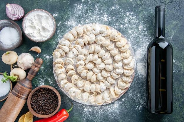 Widok z góry małe pierogi z mąką i warzywami na ciemnym tle mięso ciasto jedzenie danie kolor warzywo posiłek wino