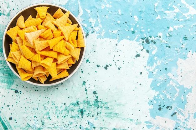 Widok z góry małe pikantne chipsy wewnątrz talerza na jasnoniebieskim tle chipsy w kolorze chrupiącym