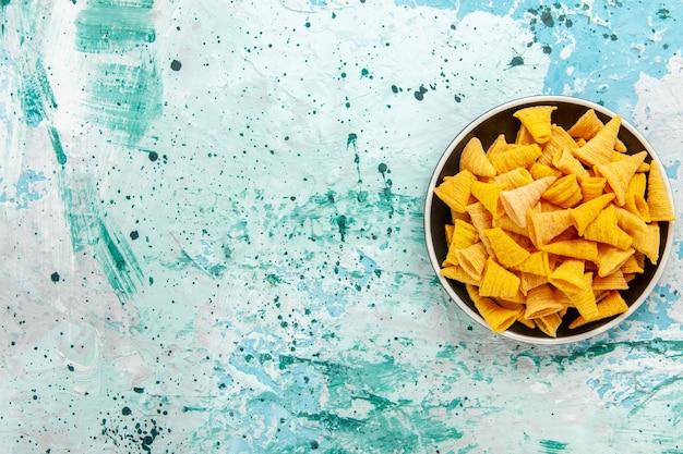 Widok z góry małe pikantne frytki wewnątrz talerza na jasnoniebieskim tle chipsy przekąska kolorowa orzeźwiająca żywność