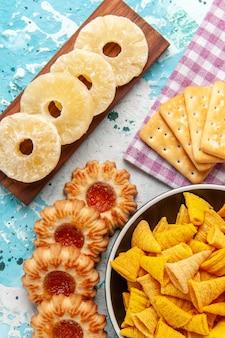 Widok z góry małe pikantne frytki z krakersami suszone krążki ananasa i ciasteczka na jasnoniebieskim stole chipsy na biurko w kolorze chrupiącej kalorii