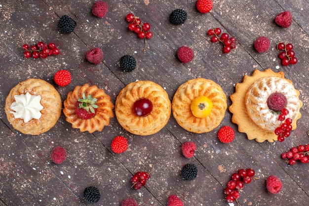 Widok z góry małe pyszne ciasta i ciasteczka z różnymi jagodami wzdłuż brązowego ciastka ciastko berry zdjęcie cookie