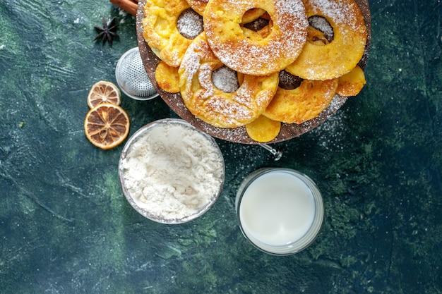 Widok z góry małe pyszne ciasta w kształcie pierścienia ananasa z mlekiem na ciemnym tle hotcake upiec ciasto ciastko ciasto owocowe