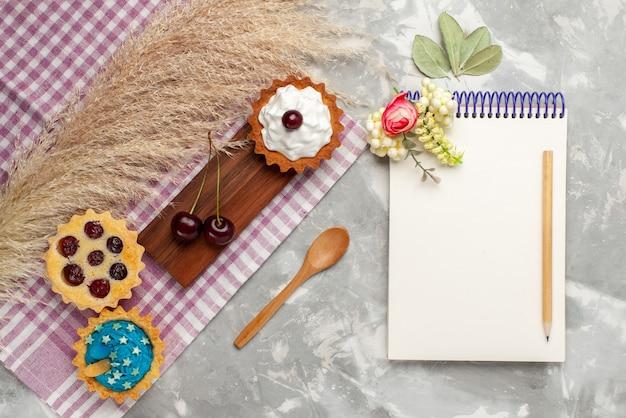 Widok z góry małe pyszne ciasta z kremem i owocami notatnik na jasnobiałym tle ciasto słodka śmietana piec owoce