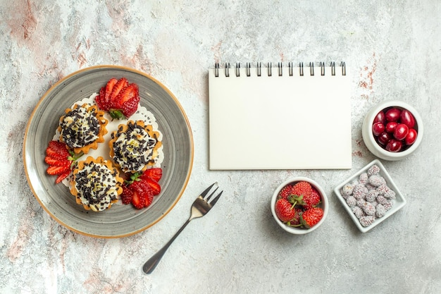 Widok z góry małe pyszne ciasta z truskawkami na białej powierzchni uroczystość urodzinowa słodki tort biszkoptowy