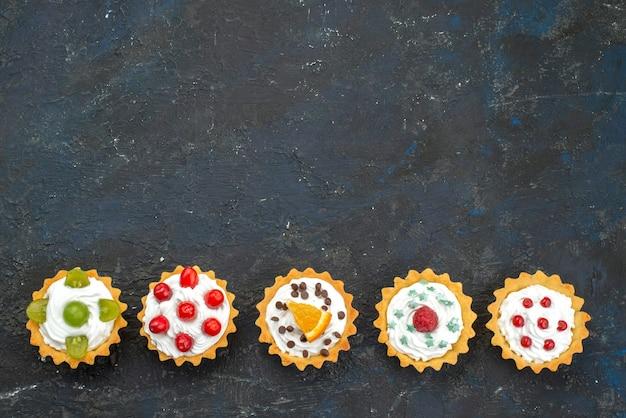 Widok z góry małe pyszne ciasta ze śmietaną i świeżymi owocami na ciemnej powierzchni słodki deser ciastko biszkoptowe