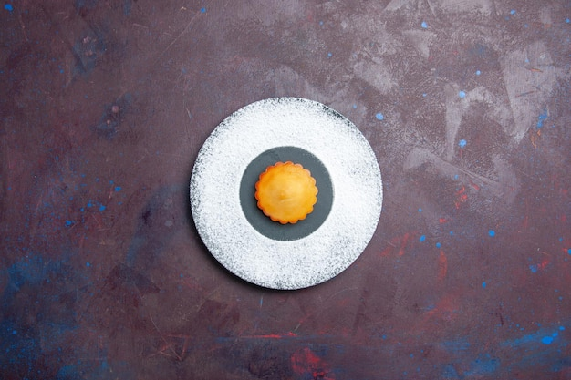 Widok z góry małe pyszne ciasto wewnątrz talerza na ciemnej powierzchni słodkie ciasto herbatnikowe ciastko z herbatą