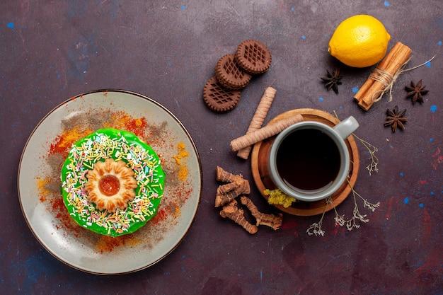 Widok z góry małe pyszne ciasto z ciasteczkami i filiżanką herbaty na ciemnej powierzchni