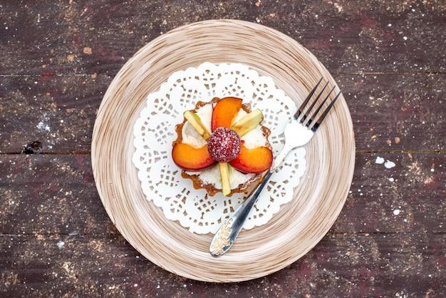 Widok z góry małe pyszne ciasto z kremem wewnątrz płyty z pokrojonymi owocami na ciemnym tle ciastko herbatnikowe ciasto owocowe