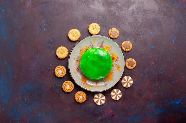 Widok z góry małe pyszne ciasto z różnymi ciasteczkami na ciemnej powierzchni