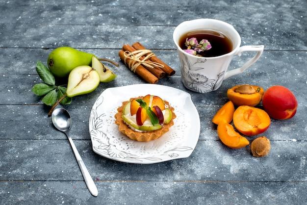 Widok z góry małe pyszne ciasto ze śmietaną i pokrojonymi owocami wewnątrz talerza z herbatą na szarym herbatniku na biurku