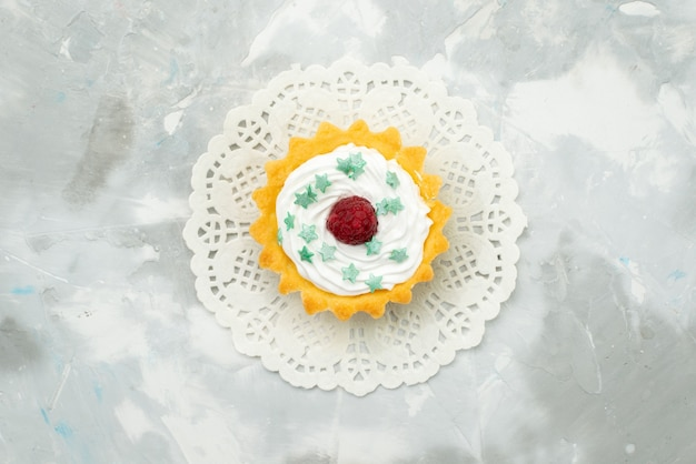 Widok z góry małe pyszne ciasto ze śmietaną na lekkim biurku słodkie ciasto