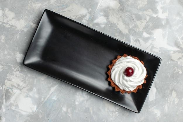 Widok z góry małe pyszne ciasto ze śmietaną wewnątrz czarnej formy na jasnym tle ciasto słodka śmietana piec owoce
