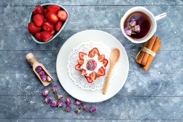 Widok z góry małe pyszne ciasto ze śmietaną wewnątrz talerza ze świeżymi pokrojonymi truskawkami i herbatą na niebiesko-szarym tle ciastko biszkoptowe ciasto owocowe