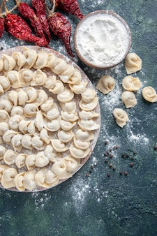 Widok z góry małe surowe knedle z mąką i warzywami na ciemnym tle mięso ciasto jedzenie danie kaloria posiłek kolor piec warzywo