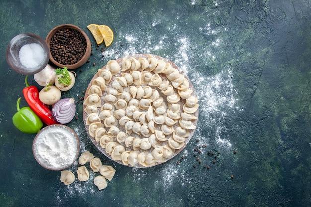 Widok z góry małe surowe knedle z mąką na ciemnym tle mięso ciasto jedzenie danie kaloria posiłek kolor piec warzywo