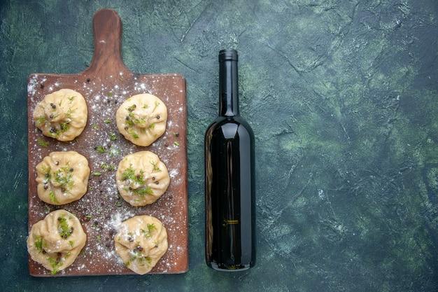 Widok z góry małe surowe pierogi na ciemnoniebieskiej powierzchni kuchnia gotowanie wina obiad ciasto danie posiłek mięso wolne miejsce