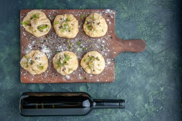 Widok z góry małe surowe pierogi na ciemnoniebieskiej powierzchni kuchnia wino gotowanie obiad ciasto danie posiłek mięso