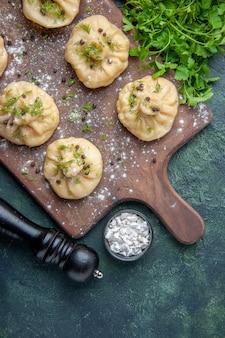 Widok z góry małe surowe pierogi z sosem pomidorowym i zieleniną na granatowym stole gotowanie ciasta obiadowego danie posiłek kuchnia mięso