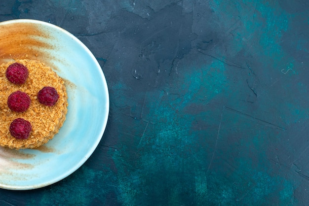 Widok z góry małego okrągłego ciasta ze świeżymi malinami wewnątrz talerza na ciemnoniebieskiej powierzchni