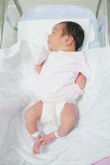 Widok z góry małej azjatyckiej nowonarodzonej dziewczynki leżącej w łóżku