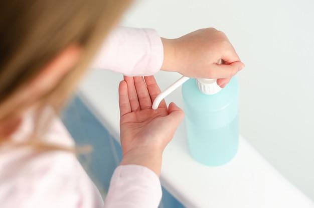 Widok z góry małej dziewczynki stosującej środek dezynfekujący do rąk w czasach globalnej pandemii wirusów
