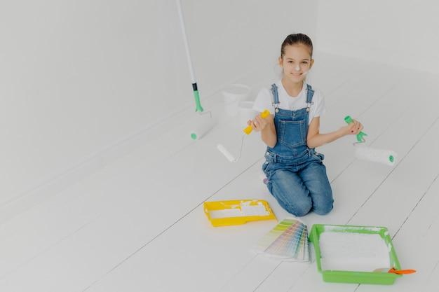 Widok z góry małej europejskiej dziewczyny w drelichowych kombinezonach stoi na kolanach